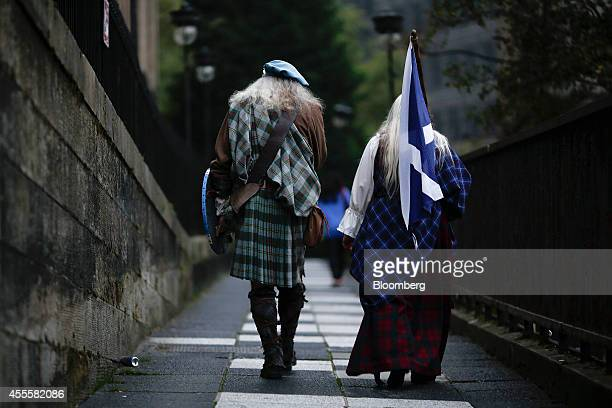 Pedestrians wearing traditional Scottish clothes including a tartan kilt carry a St Andrew's or Saltire flag the national flag of Scotland as they...