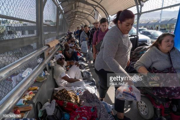 Pedestrians weave through an encampment of migrants occupying the Paso Del Norte Bridge on November 4 2018 in El Paso Texas Sending thousands of...