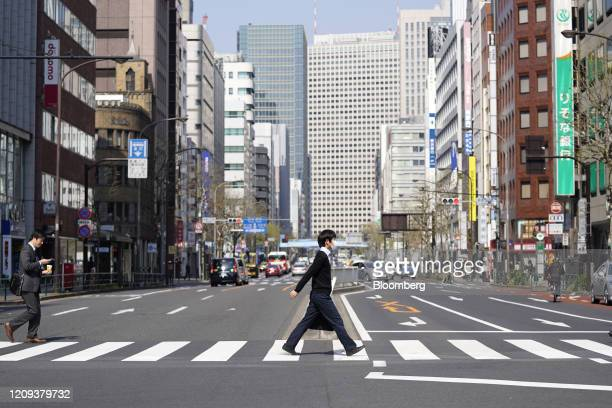 Pedestrians with and without a protective mask cross a street in the Shimbashi business district in Tokyo Japan on April 8 2020 Prime MinisterShinzo...