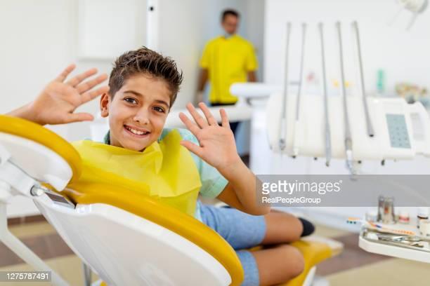 dentiste pédiatrique examinant les dents d'un petit garçon dans la chaise de dentistes à la clinique dentaire. un enfant avec un dentiste dans un cabinet dentaire. fermez-vous vers le haut des dents de petit garçon d'examen de dentiste dans la clin - 10 11 ans photos et images de collection