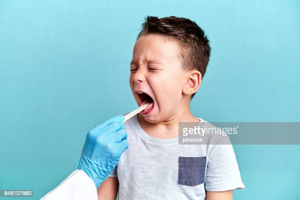 pediatric doctor examining little patient - throat photos stock photos and pictures