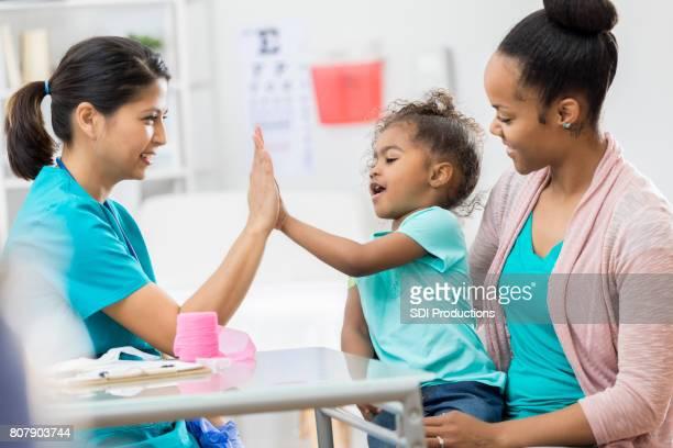 Barnsjuksköterska ger ung patient en hög fem