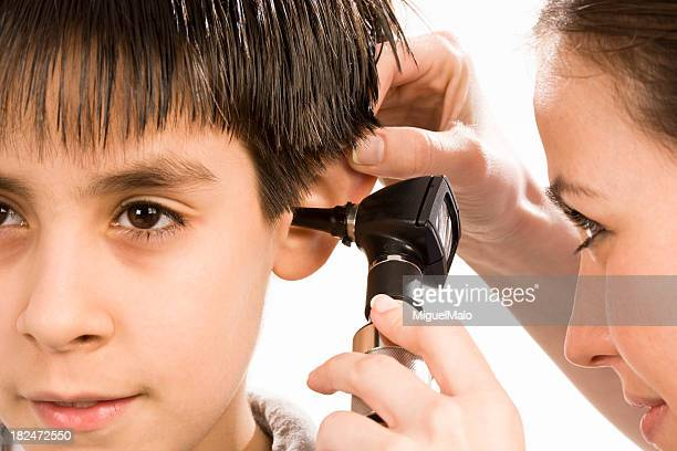pediatrician checking patient's ears - ear exam stock photos and pictures