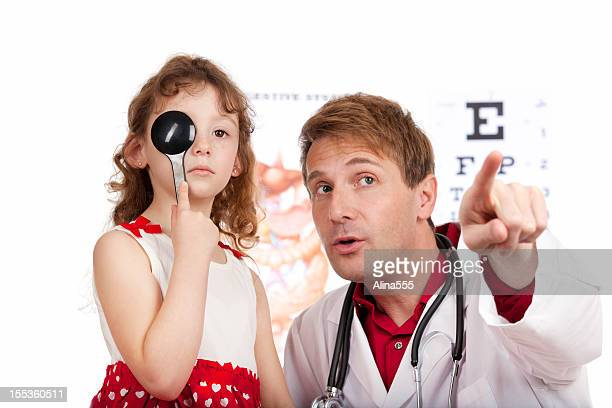 Pediatrician checking the eye sight of a young patient