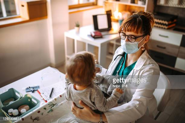 pediatrician doctor checking a temperature to a baby boy - baby changing mat stock pictures, royalty-free photos & images