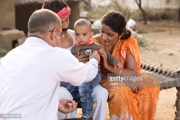 pediatrician doctor examining ill boy at village - india stock pictures, royalty-free photos & images