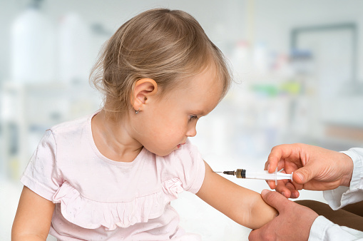 Pediatrician doctor is injecting vaccine to shoulder of baby 1066472070