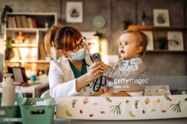 pediatrician doctor listening to heart with stethoscope - baby changing mat stock pictures, royalty-free photos & images