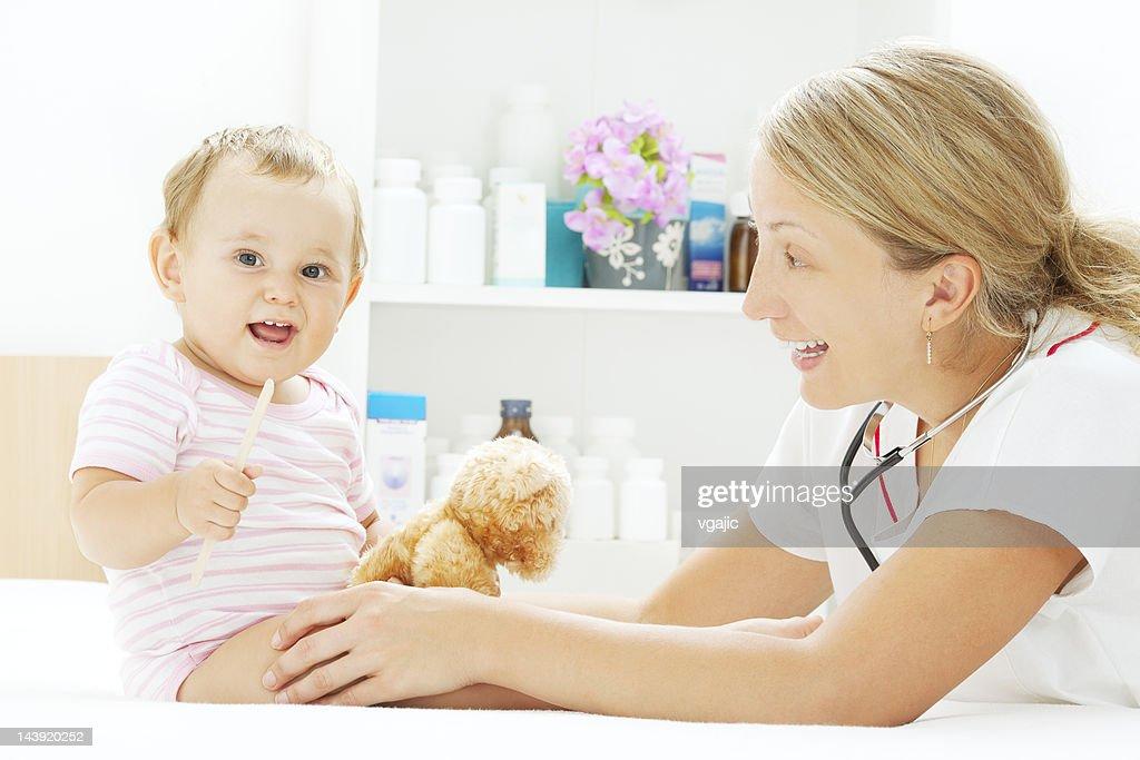 Pediatrician Doing Throat Exam Of Little Baby Girl Patient ...
