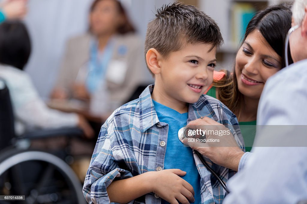 Pediatrician examines young male Hispanic patient : Stock Photo