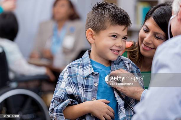 pediatrician examines young male hispanic patient - emergency medicine stock pictures, royalty-free photos & images