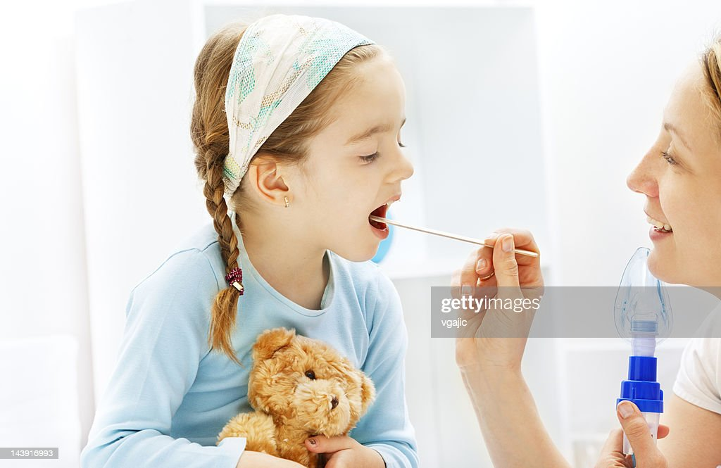 Pediatrician friendly checking little girl sore throat : Stock Photo