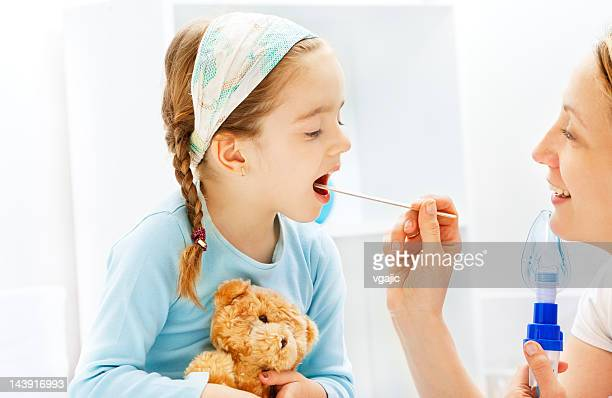 Pediatrician friendly checking little girl sore throat