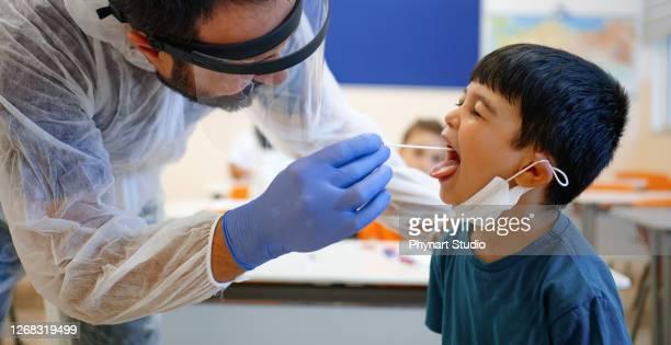 pédiatre prenant l'échantillon de test de salive - test médical photos et images de collection