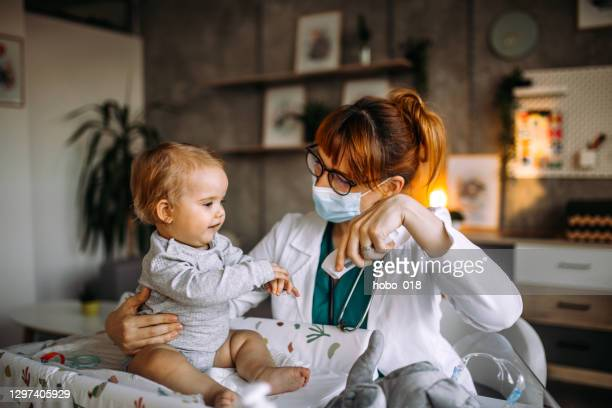 pediatrician using no contact forehad infrared thermometer - baby changing mat stock pictures, royalty-free photos & images