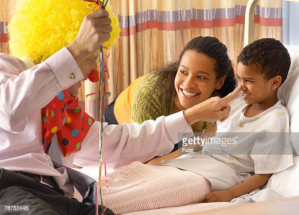 pediatrician with balloons and clown costume making young patient laugh - clown's nose stock photos and pictures