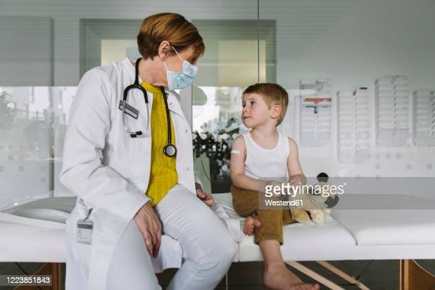 pediatrician with face mask and toddler in medical practice - pediatrician stock pictures, royalty-free photos & images