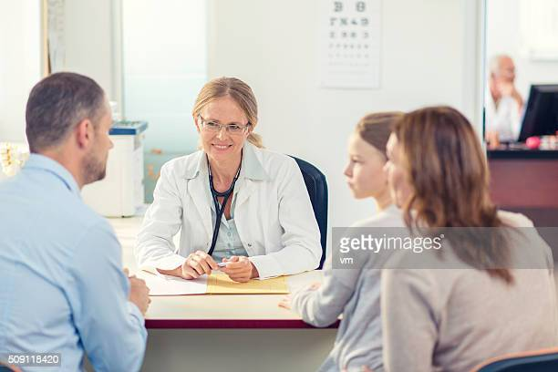 Pediatrician with family in her office