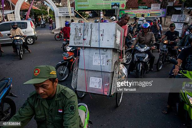 A pedicab driver carries ballot boxes for distribution to polling stations during preparations for the presidential election on July 8 2014 in...