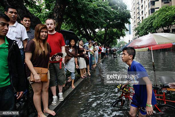 Pedicab driver offers a ride to stranded commuters in Buendia, Makati City on June 13, 2013.Heavy rains brought by the southwest monsoon hampered...
