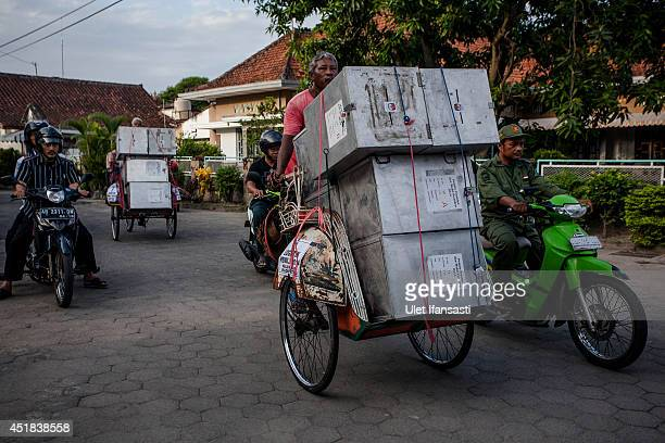 Pedicab drivers carry ballot boxes for distribution to polling stations during preparations for the presidential election on July 8 2014 in...