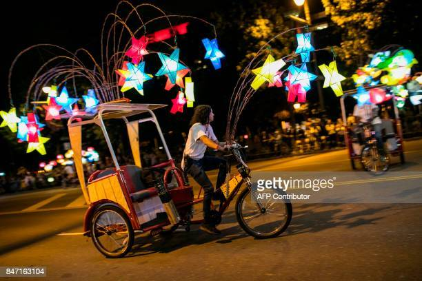Pedicab operators weave their lanterndecorated cycles in choreographed movements for the grand opening of Chinese artist Cai GuoQiang's latest work...