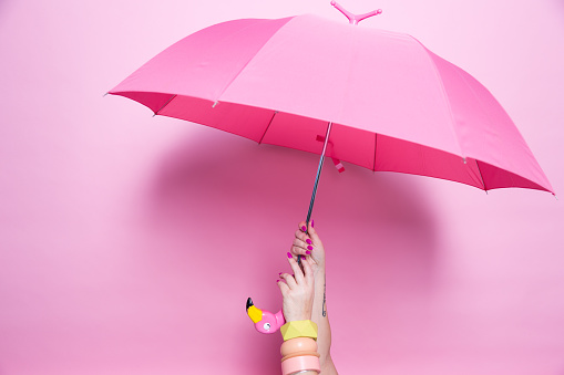A pedicured hand holds a pink umbrella against a pink background - gettyimageskorea