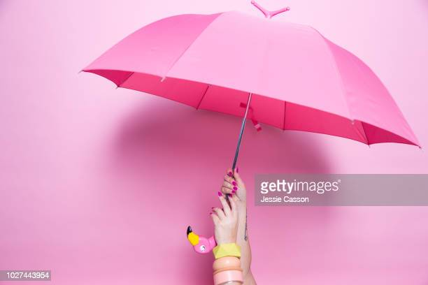 A pedicured hand holds a pink umbrella against a pink background