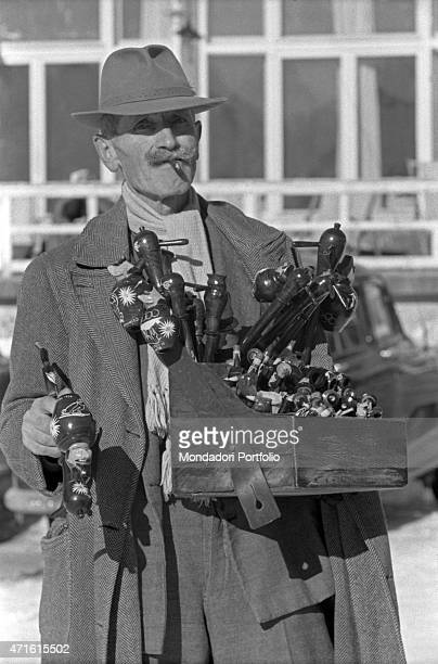 A pedlar selling pipes during the VII Olympic Winter Games Cortina d'Ampezzo 1956