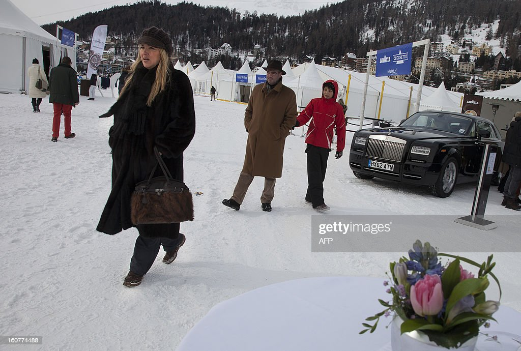 PEDRERO---Alicia Brivio, left, walks by a luxury car show at the White Turf horse racing event in St. Moritz on February 3, 2013. The American woman, married to a Swiss says 'That is so exciting when you hear the noise of the horses running in the snow, it's amazing'. The races are held on the frozen lake of the Swiss mountain resort and are famous among the jet set.
