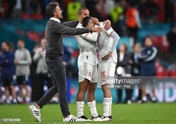 Pedri of Spain is consoled by Thiago Alcantara and Luis Enrique, Head Coach of Spain after the UEFA Euro 2020 Championship Semi-final match between...