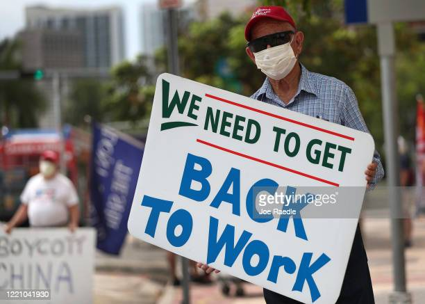 Pedro A Delgado holds as sign reading 'We need to get back to work' as he joins with other protesters in front of the Freedom Tower on April 25 2020...