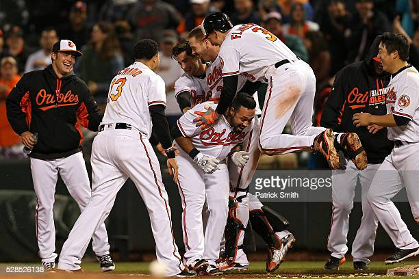 Pedro Alvarez of the Baltimore Orioles is mobbed by Ryan Flaherty and teammates after hitting the sacrifice RBI against the New York Yankees in the...
