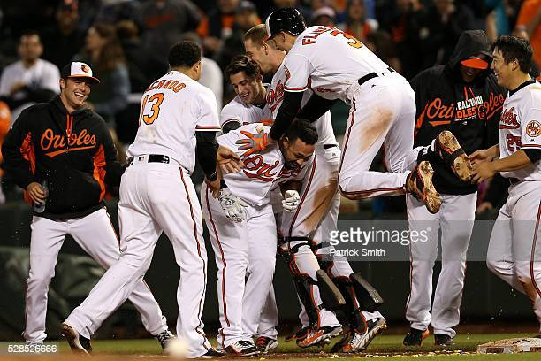 Pedro Alvarez of the Baltimore Orioles is mobbed by Ryan Flaherty and teammates after hitting a sacrifice RBI against the New York Yankees in the...