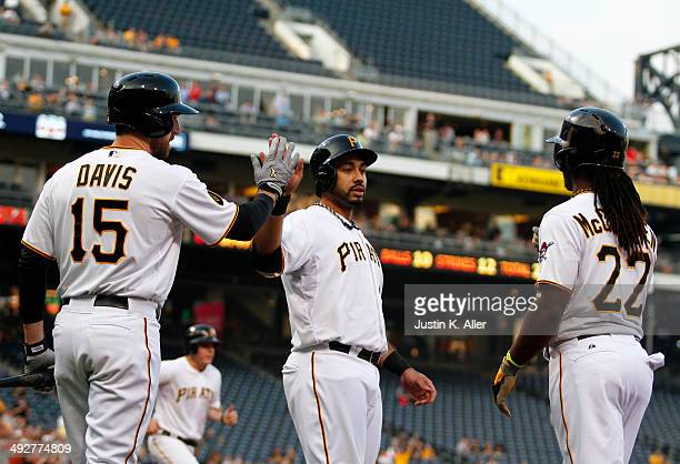 Pedro Alvarez of the Pittsburgh Pirates celebrates with Andrew McCutchen and Ike Davis after scoring on a twoRBI triple in the first inning against...