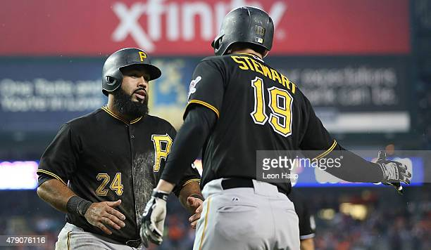 Pedro Alvarez of the Pittsburgh Pirates scores during the third inning and is congratulated by teammate Chris Stewart during the interleague game...