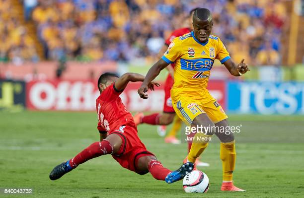 Pedro Aquino of Lobos BUAP and Enner Valencia of Tigres fight for the ball during the seventh round match between Tigres UANL and Lobos BUAP as part...