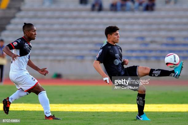 Pedro Aquino of Lobos Buap vies for the ball with Arturo Gonzalez of Monterrey during the 2017 Mexican Apertura Tournament football match at...