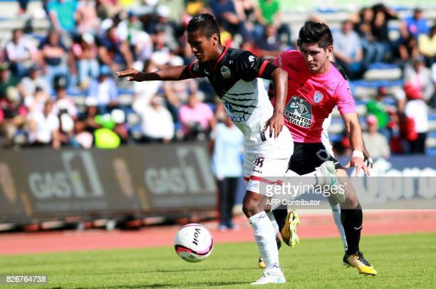 Pedro Aquino of Lobos Buap vies for the ball with Erick Aguirre of Pachuca during a Mexican Apertura 2017 Tournament football match at Universitario...