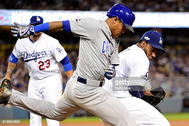 Pedro Baez of the Los Angeles Dodgers drops the ball as Addison Russell of the Chicago Cubs gets a single in the eighth inning in game five of the...