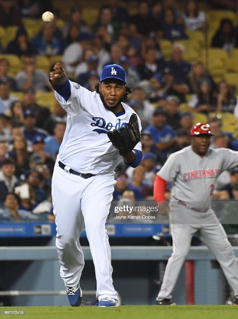 Pedro Baez #52 of the Los Angeles Dodgers fields a bunt by Alex Blandino #2 of the Cincinnati Reds and throws him out at first base in the seventh inning of the game at Dodger Stadium on May 10, 2018 in Los Angeles, California.