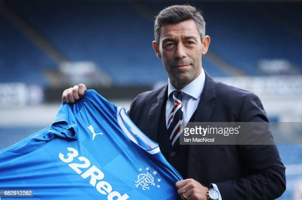 Pedro Caixinha poses with a team shirt after he is unveiled as the new manager of Rangers at Ibrox Stadium on March 13 2017 in Glasgow Scotland