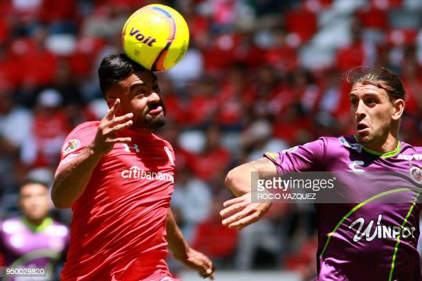 Pedro Canelo of Toluca jump for the ball with Guido Milan of Veracruz during their Mexican Clausura tournament football match at the Nemesio Diez...