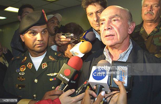 Pedro Carmona Estanga president of the business leaders association Fedecamaras speaks to the media 12 April 2002 flanked by Venzuelan Army General...