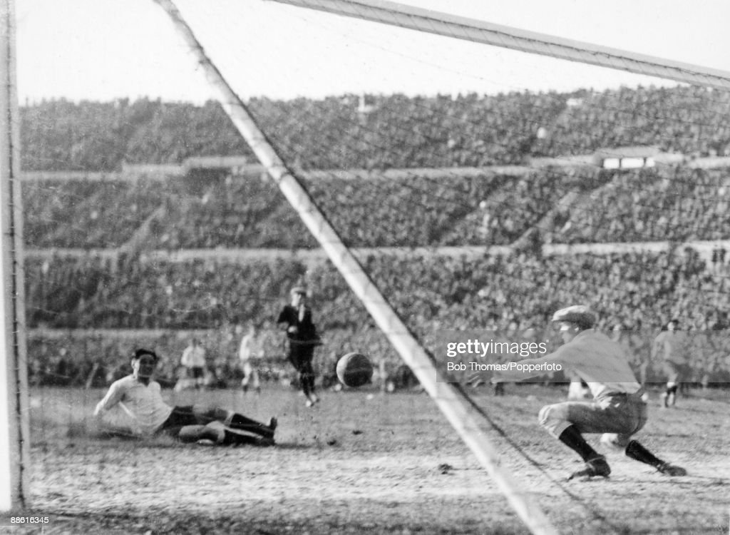 Pedro Cea (left) slides in to shoot past Argentinian goalkeeper Juan Botasso and scores Uruguay's 2nd goal during the FIFA World Cup Final between Uruguay and Argentina at the Estadio Centenario in Montevideo, 30th July 1930. Uruguay won 4-2.