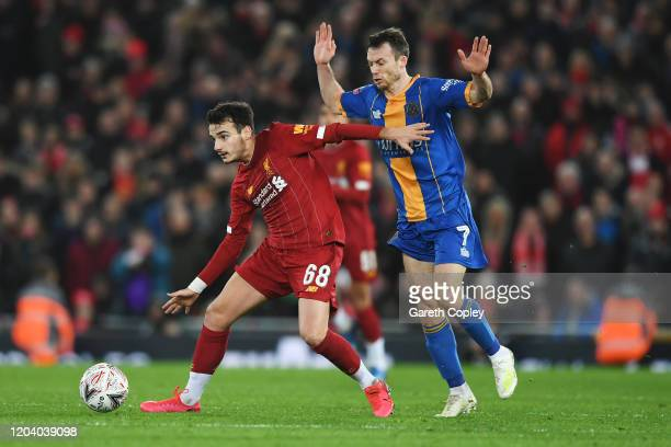 Pedro Chirivella of Liverpool is challenged by Shaun Whalley of Shrewsbury Town during the FA Cup Fourth Round Replay match between Liverpool FC and...