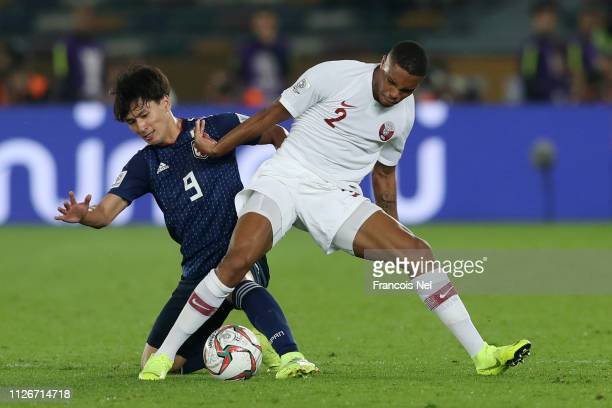 Pedro Correia of Qatar battles for possession with Takumi Minamino of Japan during the AFC Asian Cup final match between Japan and Qatar at Zayed...
