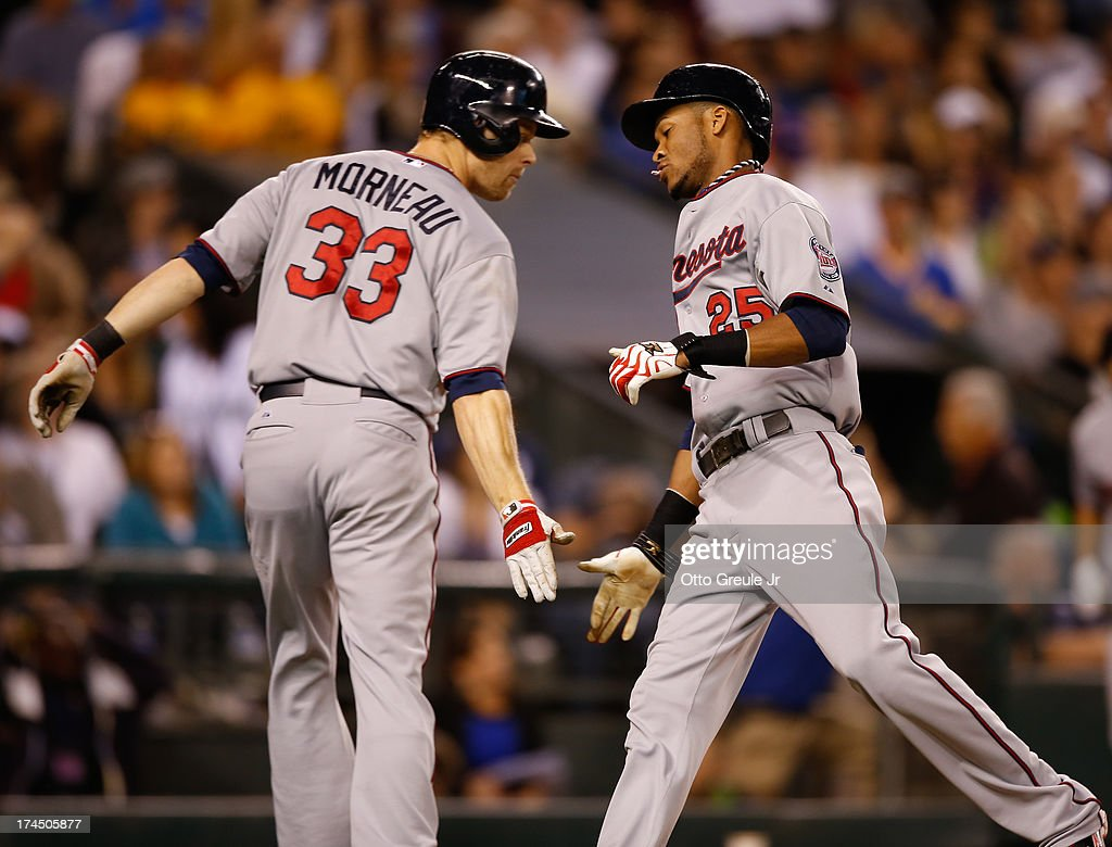 Pedro Florimon #25 of the Minnesota Twins is congratulated by Justin Morneau #33 as he scores on an RBI single by Trevor Plouffe (not pictured) to tie the game in the ninth inning against the Seattle Mariners at Safeco Field on July 26, 2013 in Seattle, Washington.