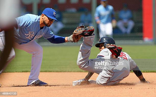 Pedro Florimon of the Minnesota Twins slides into second for a steal past the tag of Omar Infante of the Kansas City Royals in the fourth inning at...