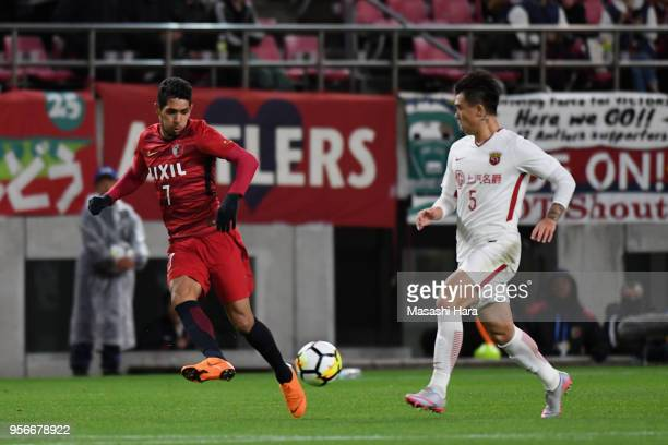 Pedro Junior of Kashima Antlers and Shi Ke of Shanghai SIPG compete for the ball during the AFC Champions League Round of 16 first leg match between...